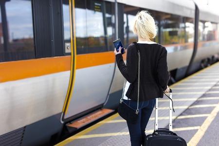 Jonge vrouw met mobiele telefoon op outdoor trein terminal met een verrijdbare koffer. Reizen met het openbaar vervoer.