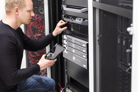 Es Ingenieur oder Berater arbeiten mit Server in Daten Rack. Shot in großen Rechenzentrum.