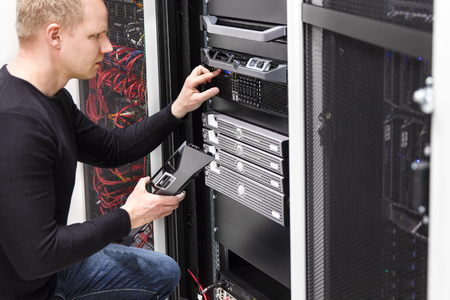 it: It engineer or consultant work with server in data rack. Shot in large datacenter. Stock Photo