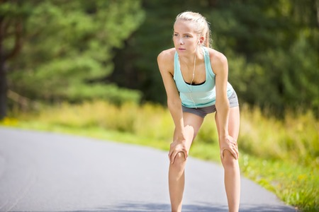 slim women: Young athletic woman runner rest after running outdoor in the forest. Tired girl holding her hands on the knees. Stock Photo