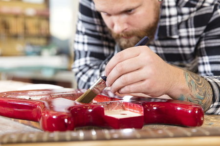 causal clothing: Close-up of a adult crafts man  with a guitar in a workshop for painting. Stock Photo