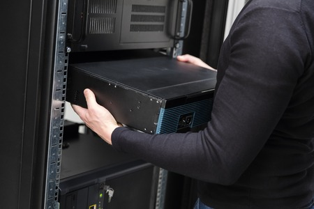 computer network: It engineer or technician work with network equipment in data rack. Shot in large datacenter. Stock Photo