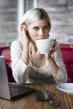 looking into camera: Focused woman with laptop and smart phone drinking coffee and doing business or study in a cafe. Looking into camera. Stock Photo