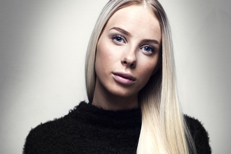 studio photography: Beautiful young fashion woman with long blonde hair and black furry design jacket. Studio photography. Gray backround.