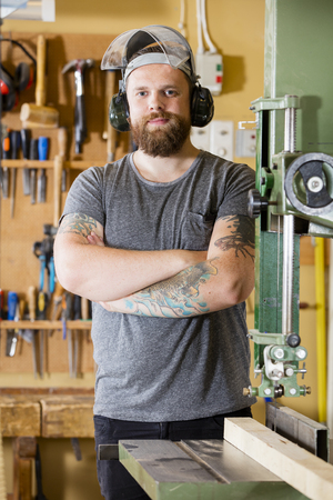 Portrait of smiling carpenter using band saw for cutting wood in a workshop for woodwork.