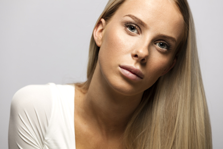 studio photography: Beautiful young casual woman with long blonde hair and white top. Studio photography. Gray backround.