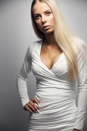 junge nackte mädchen: Mode-Foto einer schönen jungen Frau mit blonden Haaren in einem weißen Kleid. Natürliche Studio retuschiert Porträt.