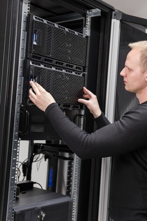 datacenter: It engineer or technician work with servers in data rack. Shot in large datacenter.