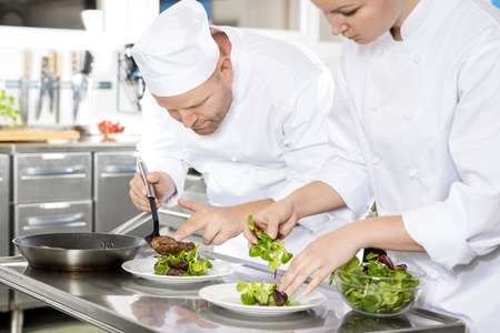 garnish: Professional chefs prepares beef meat dish in a professional kitchen at gourmet restaurant or hotel.