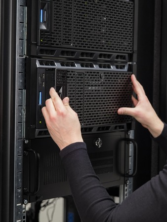 it technician: It engineer or technician work with servers in data rack. Shot in large datacenter.
