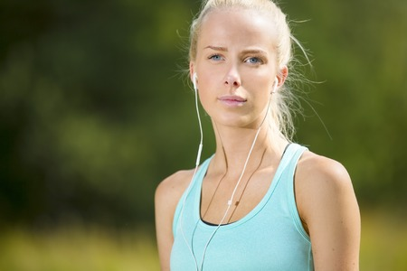 motivated: Motivated and cheerful young blonde woman taking a break after workout. Listens to music.