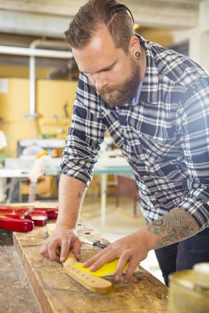 planos electricos: Artesano usando papel de lija en un cuello de la guitarra en un taller de madera. Hombre de trabajo duro con el tatuaje y la barba se trabaja con instrumentos musicales. Foto de archivo