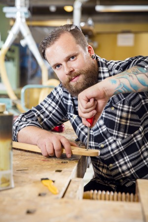 planos electricos: Smiling carpenter using file on a guitar neck in a workshop for wood. Man with tattoo and beard working with musical instruments.