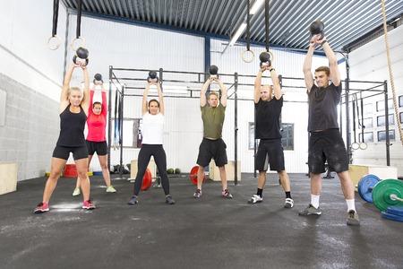 deportista: Grupo de entrenamiento con entrenador personal e instructor en un gimnasio. Entrenamiento del peso de pesas rusas en el gimnasio.