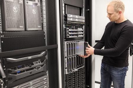 red informatica: Es ingeniero o consultor que trabaja con la instalaci�n de un servidor blade en el bastidor de datos. Un disparo en centro de datos empresarial. Foto de archivo