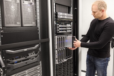 computer equipment: It engineer or consultant working with installation of a blade server in data rack. Shot in enterprise datacenter.