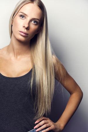 blonde yeux bleus: Confiant, causal et naturel jeune femme blonde tenant une main sur la hanche. Natural retouchés haute résolution photo de studio. Banque d'images