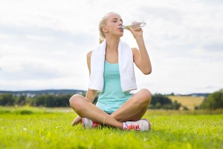 agua potable: Delgada mujer rubia tomando un descanso después del entrenamiento. Sentado con una toalla alrededor del cuello y agua potable después del entrenamiento.