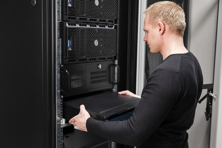 it technician: It engineer or technician work with network equipment in data rack. Shot in large datacenter. Stock Photo