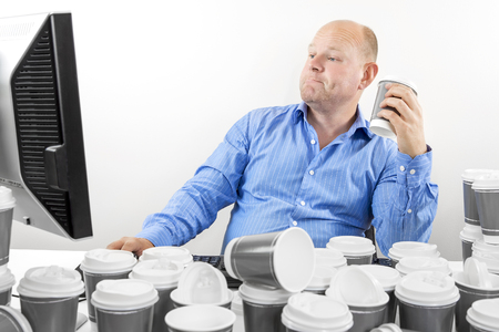 too much: Overworked and exhausted office worker or businessman high on coffeine. Man drinks too much coffee. Stock Photo