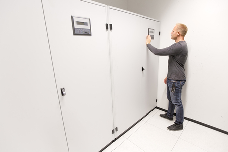 cooling system: Service technician or consultant maintains and adjusts air cooling system in large datacenter