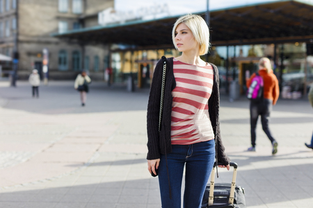 public transport: Blonde young woman at a train terminal walking with a wheeled suitcase. Traveling with public transport.