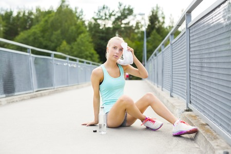 exhausted: Young athletic female runner rests after running or jogging training outdoor. Drinks water and dries her face with a towel on a bridge.