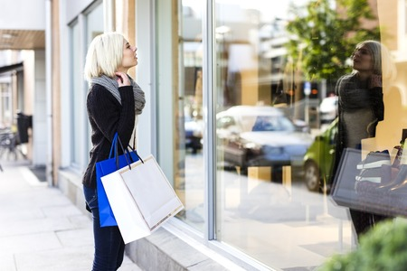 Young woman standing outside a shop and looking at the products inside the window. Shopping in the city.