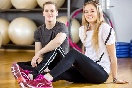 Feliz mujer joven y el hombre toma un descanso de entrenamiento en el gimnasio de fitness. Equipo de descanso después del entrenamiento.