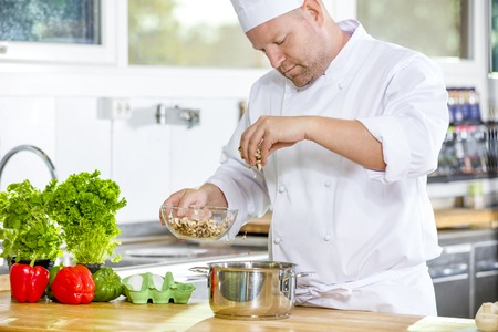 garnishing: Professional chef chops up vegetables and makes food in industrial kitchen.