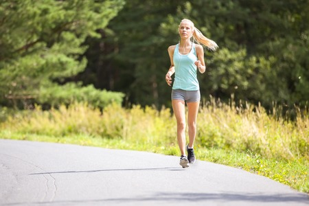 runs: Healthy and slim blonde woman runs or jogs on a road in the forest. Workout outdoor a summer evening. Stock Photo