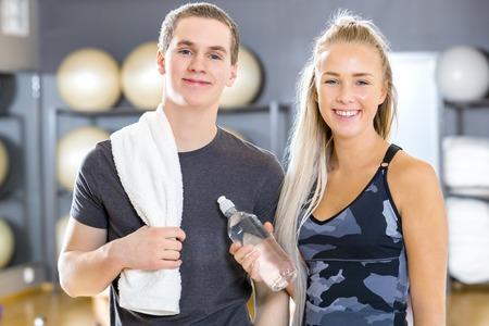 juventud: mujer joven y el hombre toma un descanso de entrenamiento en el gimnasio de fitness sonriendo. Equipo de descanso después del entrenamiento.