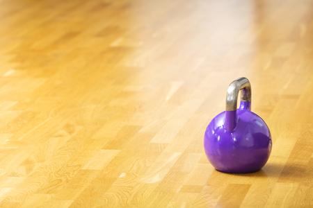 hard core: Heavy purple kettlebell weight stands on parquet floor.  Workout background.
