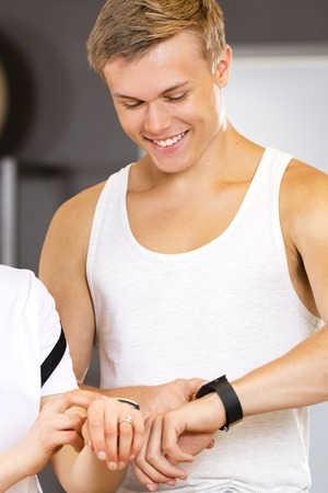 trainer device: Two young smiling people having a break looking at the wearable health monitoring sports clock with training statistics. Technology and workout at the fitness gym. Stock Photo