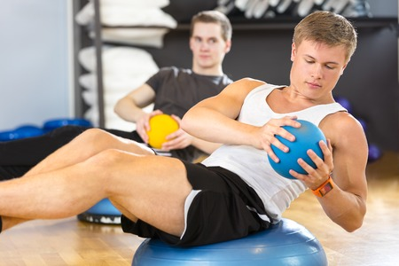 sit ups: Focused young men doing sit ups on half ball and with medicine ball as weight at the fitness class. Core muscle and balance workout. Team and motivation at the gym. Stock Photo