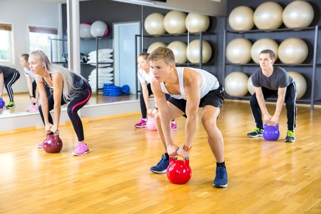 hard core: Group workout at a fitness center. Kettlebell weight workout at the gym.
