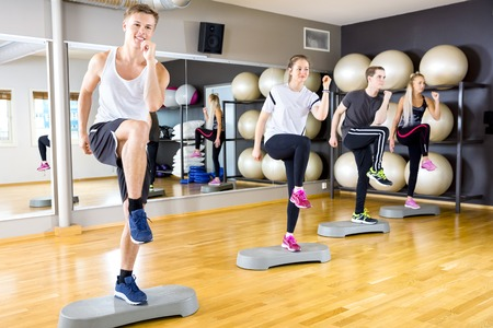 step by step: Focused and dedicated people in team raises legs at step platform in a fitness gym class. Stamina and body coordination workout. Teamwork and motivation. Stock Photo