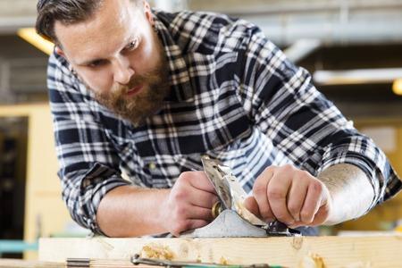 planos electricos: artesano trabajando duro trabaja con la alisadora en un taller de carpintería. Hombre hermoso con el tatuaje y la barba. Centrarse en la cepilladora.
