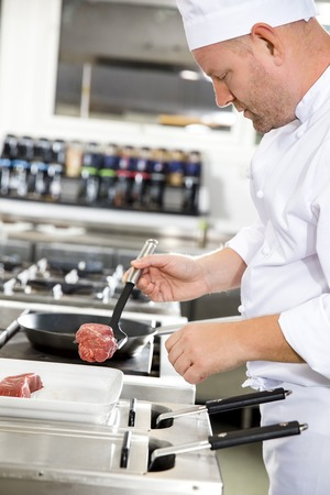 gourmet kitchen: Close-up of a chef prepares beef steak dish in a pan at a professional kitchen. Gourmet restaurant or hotel.