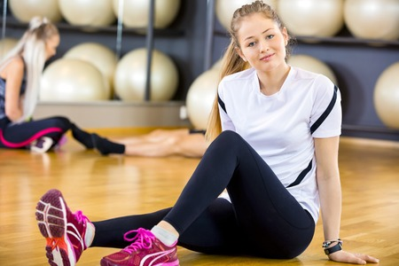 slim girl: Young woman taking a break from training at the fitness gym.  Workout team resting in the background.