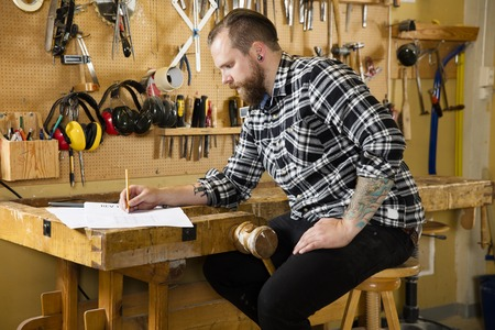 causal clothing: Adult craftsman sits and looks at plan drawings in a work shop for wood work and construction. Carpenter designs and prepares new work.