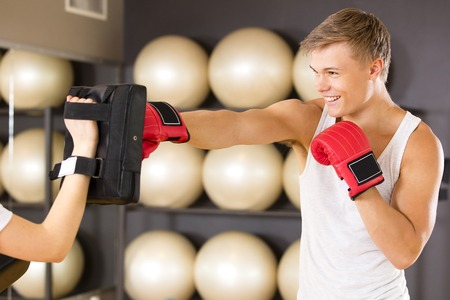 Two young and focused people trains boxing in pairs. Sparring as workout at the fitness gym. Stock Photo