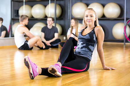 slim girl: Smiling young woman taking a break from training at the fitness gym.  Workout team resting in the background.