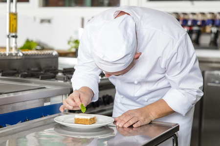 decorates: Close-up of a professional male chef who decorates dessert cake with lemon leaf. Large industry kitchen.