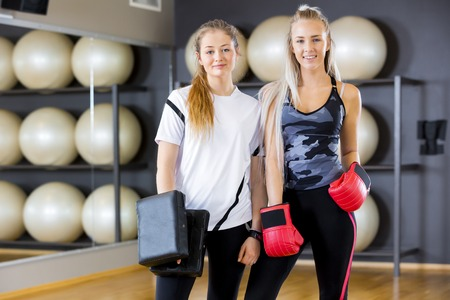 girl punch: Environmental portrait of two young women takes a break from boxing training. Sparring in pairs as workout at the fitness gym.