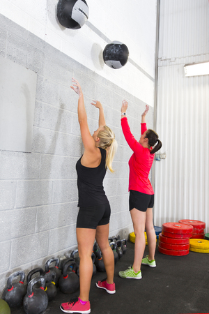 cross bar: Young women team throw medicine balls at a wall in fitness gym center. Stock Photo