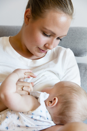 Portrait of a loving mother in sofa breastfeeding baby girl. Newborn child fed with breast milk by mom. Stock Photo