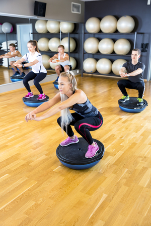 half ball: Focused young people in workout team doing squats on half ball in a fitness gym class. Core muscle and balance workout. Teamwork and motivation.