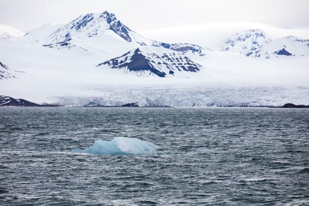 calving: Close-up of the large and massive Borebreen glacier from the sea. Arctic environment in Oscar II Land at Spitsbergen, Svalbard. Melting ice and global warming. Stock Photo