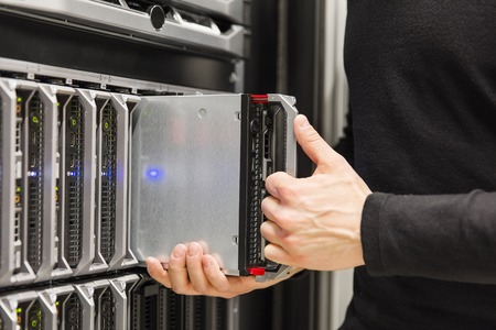server side: It engineer or consultant working with blade server installation in data rack. Shot in enterprise datacenter.